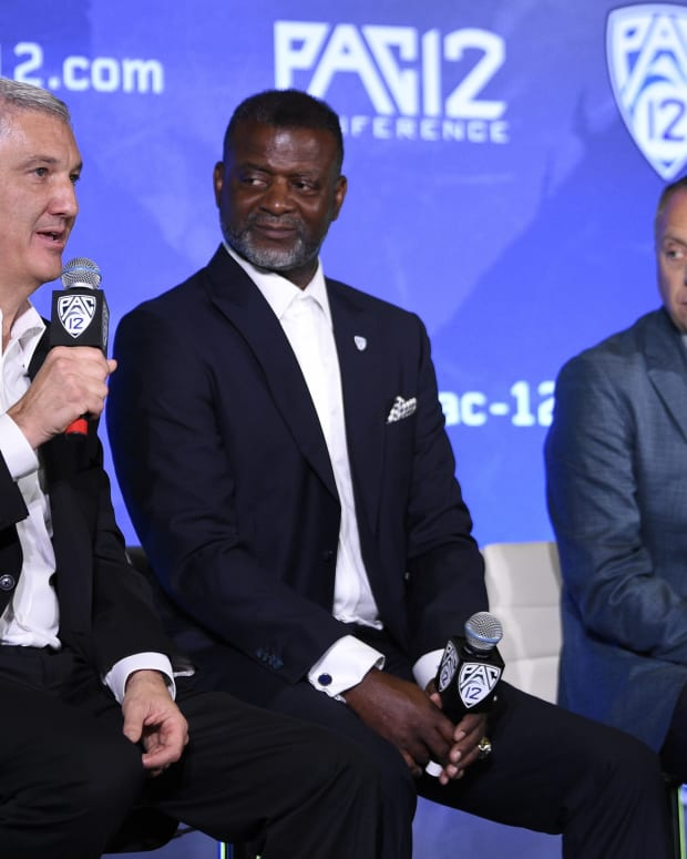 Pac-12 commissioner George Kliavkoff speaks to the media, joined by league exec Merton Hanks and Oregon athletic director Rob Mullens.