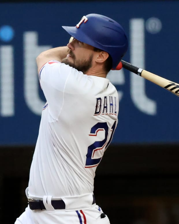 Apr 26, 2021; Arlington, Texas, USA; Texas Rangers left fielder David Dahl (21) hits an rbi sacrifice fly during the first inning against the Los Angeles Angels at Globe Life Field.