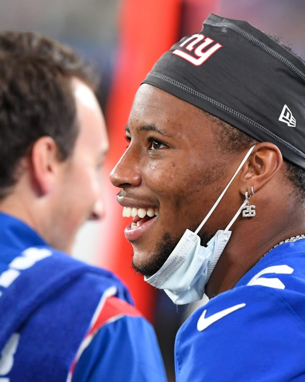 Aug 14, 2021; East Rutherford, New Jersey, USA; New York Giants running back Saquon Barkley (26) on the sidle line watches the game against the New York Jets during the second half at MetLife Stadium. Dennis Schneidler-USA TODAY Sports