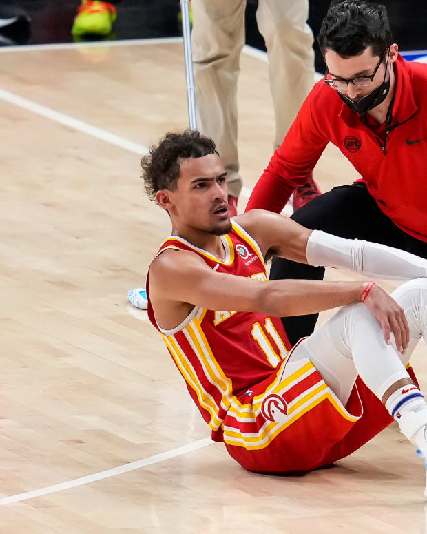 Atlanta Hawks guard Trae Young is attended to after injuring his foot by accidentally stepping on an official's foot against the Milwaukee Bucks.