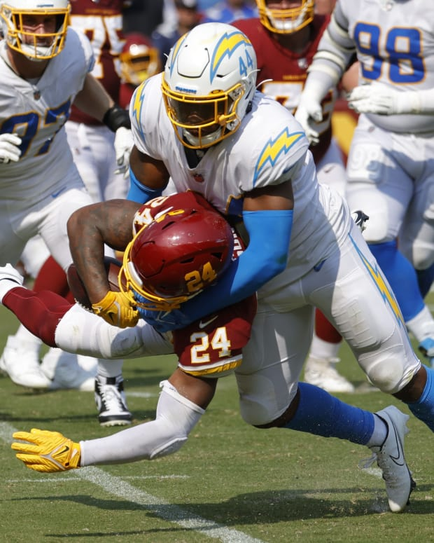 Sep 12, 2021; Landover, Maryland, USA; Washington Football Team running back Antonio Gibson (24) fumbles the ball on a hit by Los Angeles Chargers linebacker Kyzir White (44) in the fourth quarter at FedExField.