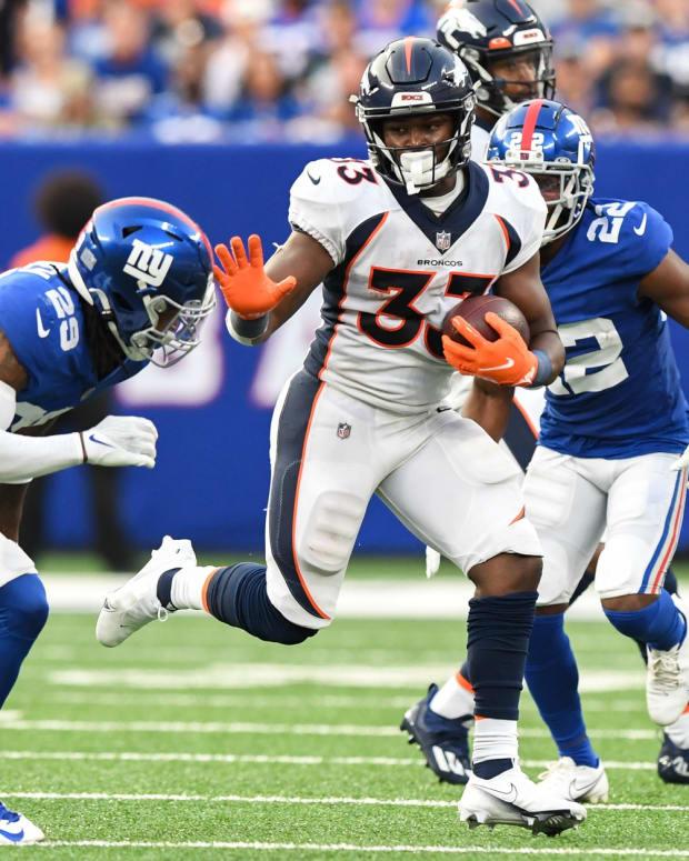Denver Broncos running back Javonte Williams (33) stiff arms New York Giants safety Xavier McKinney (29) during the second half at MetLife Stadium.