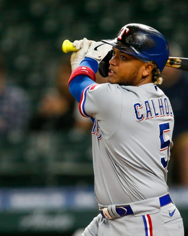 May 27, 2021; Seattle, Washington, USA; Texas Rangers designated hitter Willie Calhoun (5) hits a triple against the Seattle Mariners during the sixth inning at T-Mobile Park.