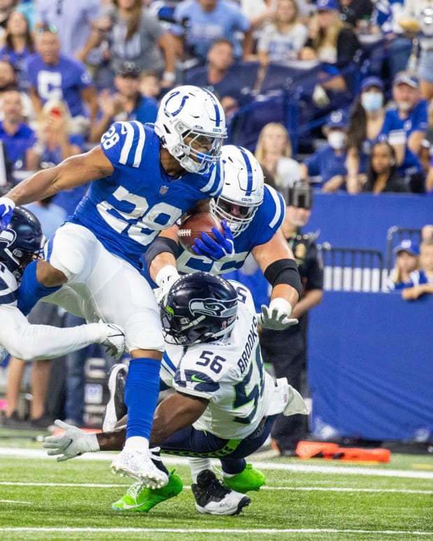 Sep 12, 2021; Indianapolis, Indiana, USA; Indianapolis Colts running back Jonathan Taylor (28) runs the ball while Seattle Seahawks defensive end Kerry Hyder (51) and linebacker Jordyn Brooks (56) defend in the first quarter at Lucas Oil Stadium.