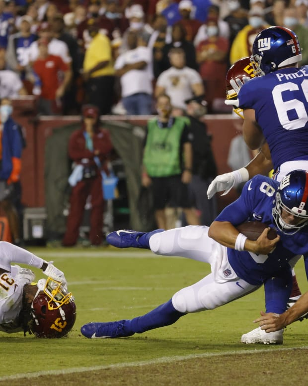 Sep 16, 2021; Landover, Maryland, USA; New York Giants quarterback Daniel Jones (8) runs for a touchdown as Washington Football Team safety Kamren Curl (31) attempts the tackle in the first quarter at FedExField.