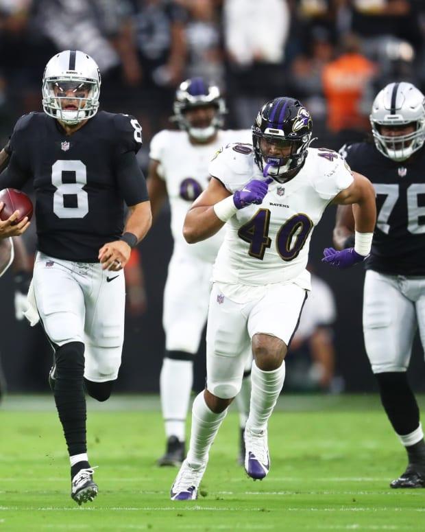 Las Vegas Raiders quarterback Marcus Mariota (8) runs the ball ahead of Baltimore Ravens linebacker Patrick Queen (6) defensive back DeShon Elliott (32) and linebacker Malik Harrison (40) during the first half at Allegiant Stadium.