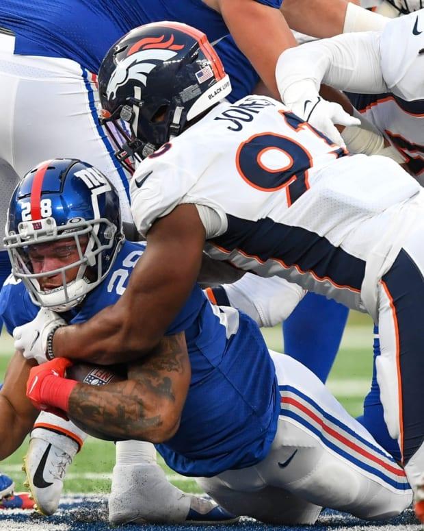 Denver Broncos defensive end Dre'Mont Jones (93) tackles New York Giants running back Devontae Booker (28) during the second half at MetLife Stadium.