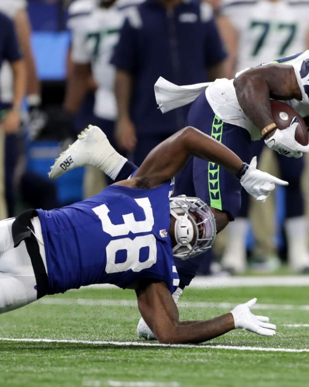 Seattle Seahawks running back Chris Carson (32) evades a tackle by Indianapolis Colts defensive back T.J. Carrie (38) on Sunday, Sept. 12, 2021, during the regular season opener at Lucas Oil Stadium in Indianapolis.