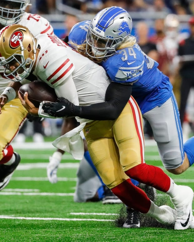 Detroit Lions linebacker Alex Anzalone (34) tackles San Francisco 49ers quarterback Jimmy Garoppolo (10) during the first half at Ford Field in Detroit on Sunday, Sept. 12, 2021.