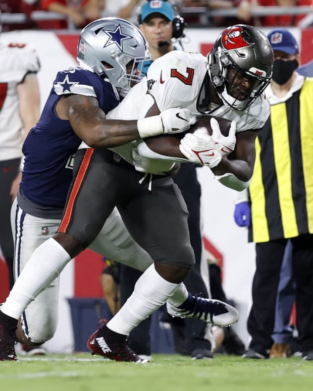 Sep 9, 2021; Tampa, Florida, USA; Tampa Bay Buccaneers running back Leonard Fournette (7) runs with the ball against Dallas Cowboys linebacker Micah Parsons (11) during the second half at Raymond James Stadium. Mandatory Credit: Kim Klement-USA TODAY Sports