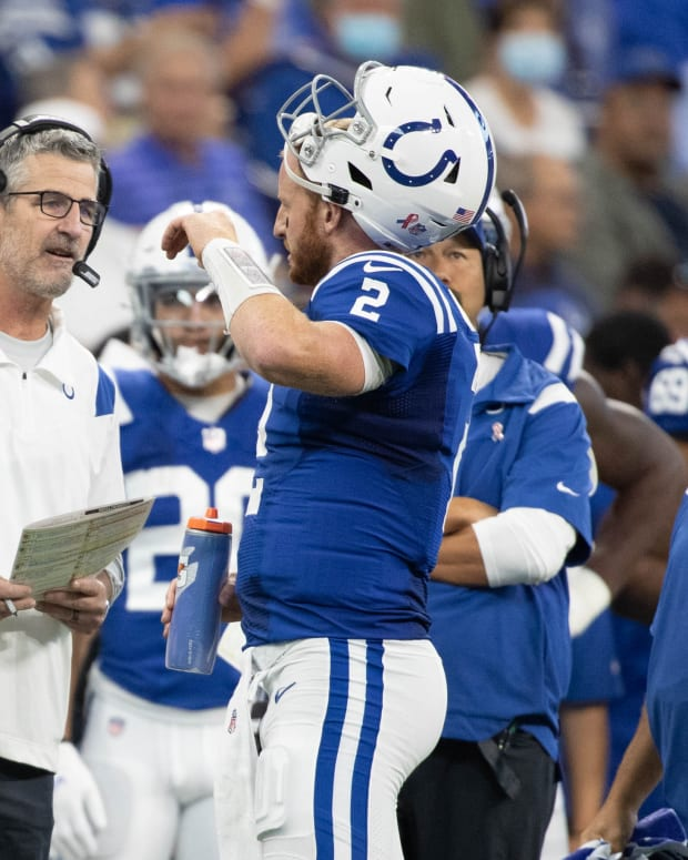 Sep 12, 2021; Indianapolis, Indiana, USA; Indianapolis Colts head coach Frank Reich and Indianapolis Colts quarterback Carson Wentz (2) talk during a timeout in the second quarter against the Seattle Seahawks at Lucas Oil Stadium. Mandatory Credit: Trevor Ruszkowski-USA TODAY Sports
