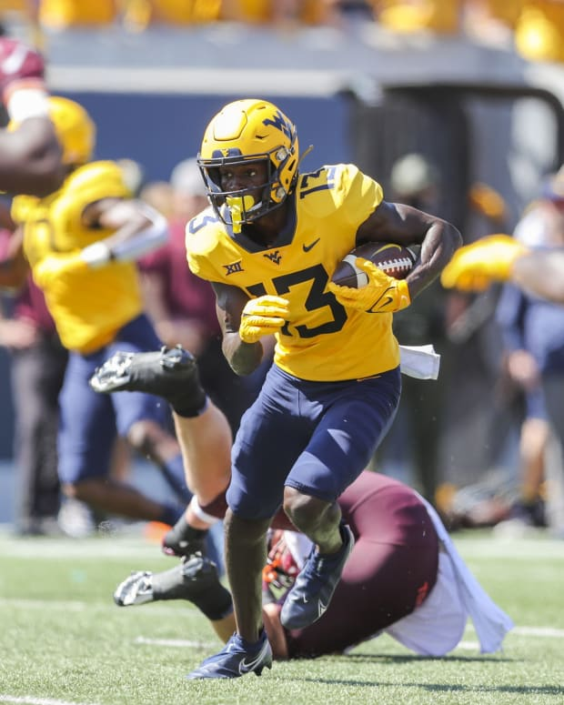 Sep 18, 2021; Morgantown, West Virginia, USA; West Virginia Mountaineers wide receiver Sam James (13) catches a pass and runs for a touchdown during the second quarter against the Virginia Tech Hokies at Mountaineer Field at Milan Puskar Stadium.