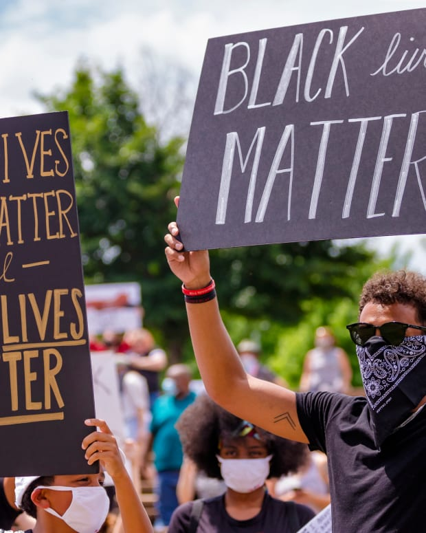 Norman native and Atlanta Hawk basketball player Trae Young, right, gathers with others protesters as they carry signs during a protest at Andrews Park on Monday, June 1, 2020.