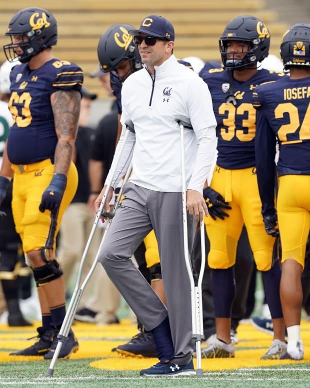 Justin Wilcox on crutches Darren Yamashita