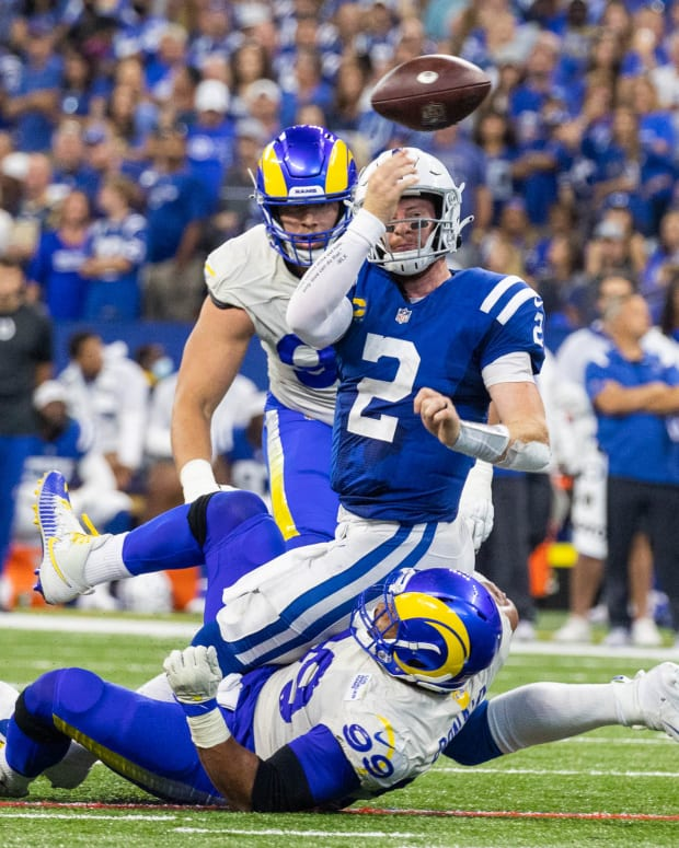 Sep 19, 2021; Indianapolis, Indiana, USA; Indianapolis Colts quarterback Carson Wentz (2) passes the ball while Los Angeles Rams defensive end Aaron Donald (99) defends in the second half at Lucas Oil Stadium. Indianapolis Colts quarterback Carson Wentz (2) did not return after this tackle. Mandatory Credit: Trevor Ruszkowski-USA TODAY Sports