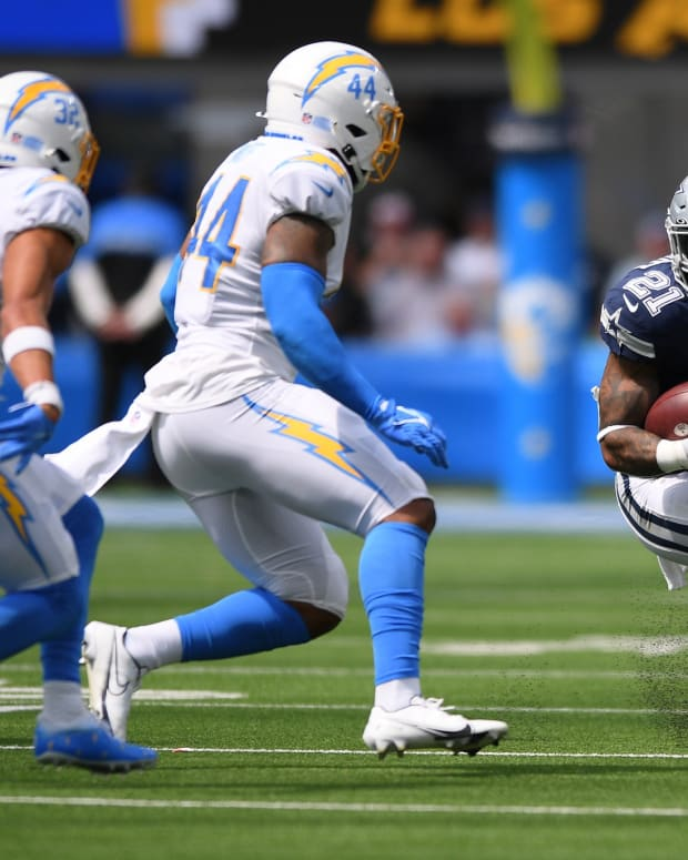 Sep 19, 2021; Inglewood, California, USA; Dallas Cowboys running back Ezekiel Elliott (21) runs the ball while defended by Los Angeles Chargers outside linebacker Kyzir White (44) and safety Alohi Gilman (32) during the first quarter at SoFi Stadium.