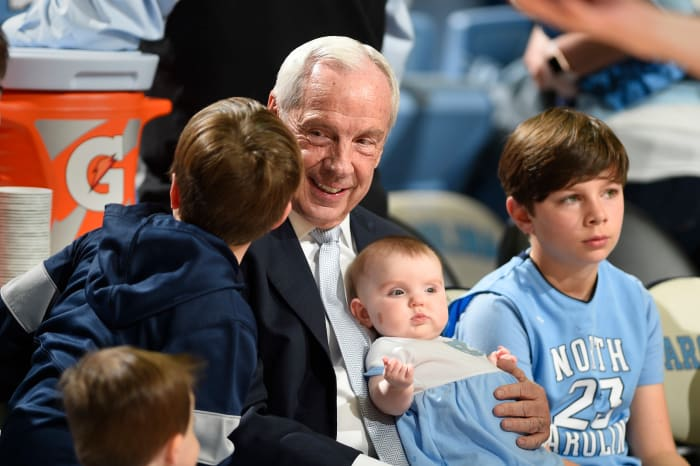 North Carolina tar heels head coach Roy Williams holds his granddaughter Kenzie Newlin before the game at the Dean Smith center.