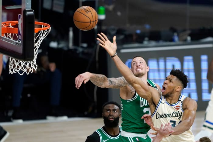 Giannis Antetokounmpo de Milwaukee Bucks, à droite, se dirige vers le panier alors que Daniel Theis des Boston Celtics défend pendant la seconde moitié d'un match de basket NBA vendredi 31 juillet 2020,