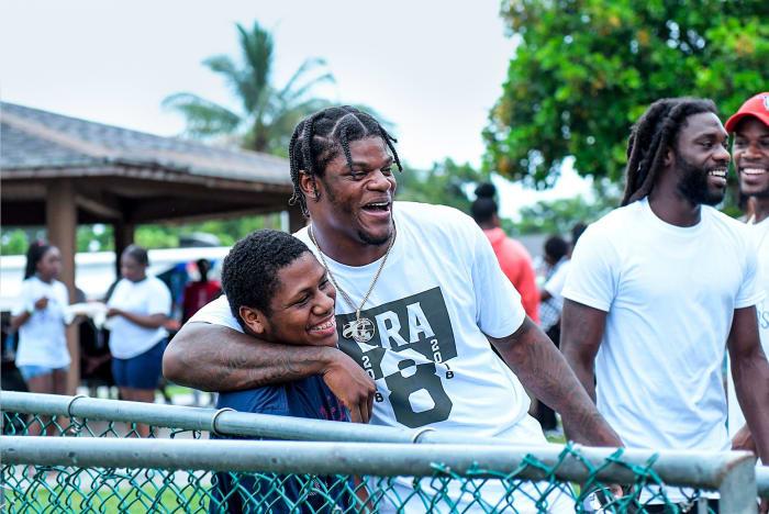Lamar Jackson poses for a photo with a kid at McNair Park