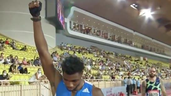 Noah Lyles raises his fist with a black glove before the start of the Monaco Diamond League men's 200 meters.