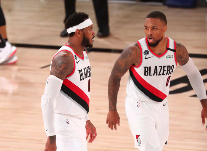 Portland Trail Blazers guard Damian Lillard (0) and forward Carmelo Anthony (00) talk in the second half against Los Angeles Lakers in game three of the first round of the 2020 NBA Playoffs