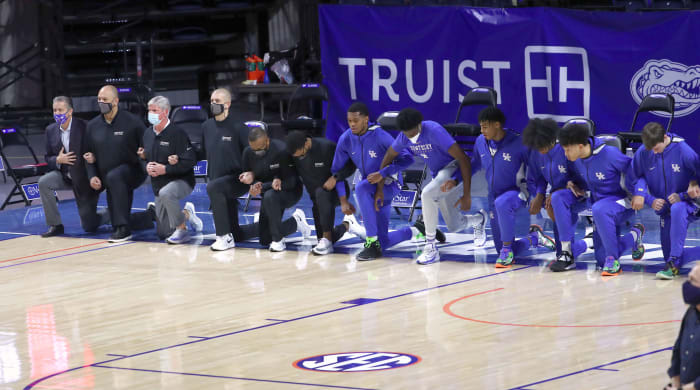 Kentucky Wildcats coaches and players kneel during the national anthem before the game against the Florida Gators on Jan. 9, 2021.