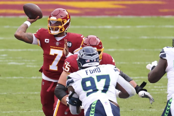 "Washington Football Team quarterback Dwayne Haskins Jr. (7) passes the ball as Seattle Seahawks defensive tackle Poona Ford (97) defends in the second quarter at FedExField. The back of Ford's helmet reads, ""Breonna Taylor."" © Geoff Burke-USA TODAY Sports"