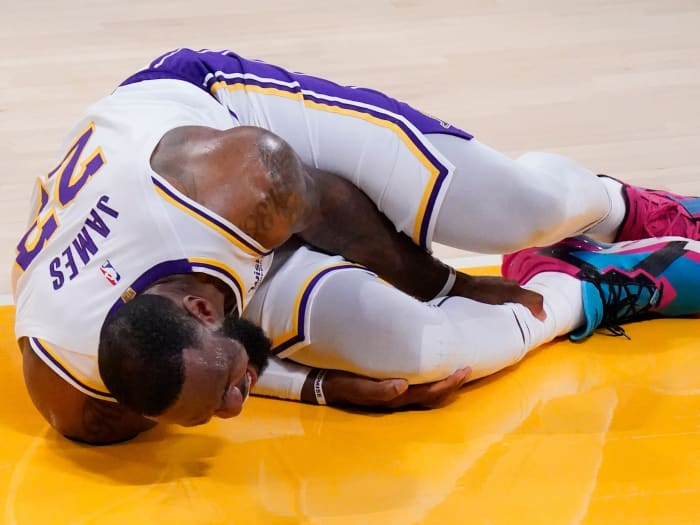 LeBron James grabs his ankle after injuring himself
