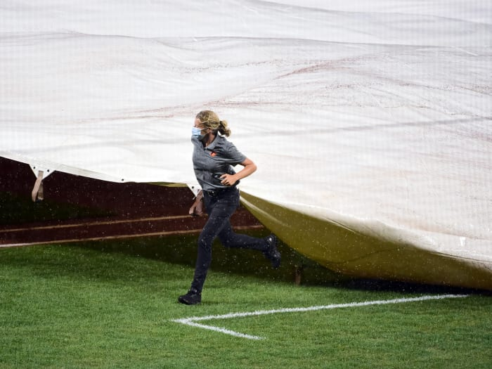 July 30, 2020;  Baltimore, Maryland, United States;  Baltimore Orioles main fielder Nicole Sherry (center) covers the field with the canvas during a rain delay in a game against the New York Yankees at Oriole Park at Camden Yards.