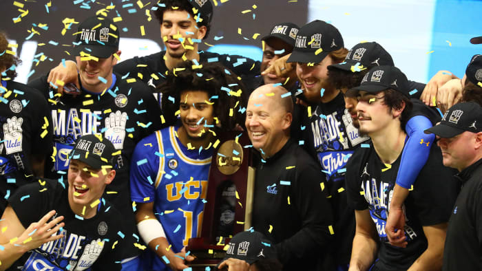UCLA's Mick Cronin celebrates with his team after beating Michigan