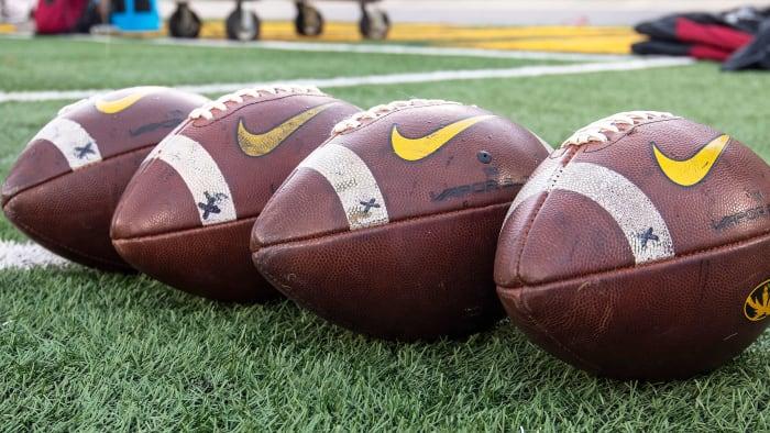 College footballs sit on ground