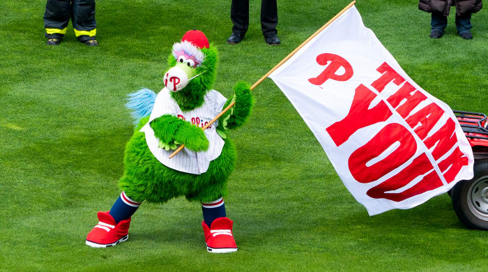 April 1, 2021;  Philadelphia, Pennsylvania, United States;  The Phillie Phanatic waves a flag to thank the first responders before a game between the Philadelphia Phillies and the Atlanta Braves at Citizens Bank Park.