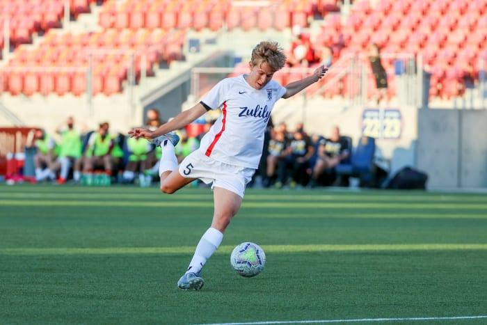 Quinn kicks a soccer ball