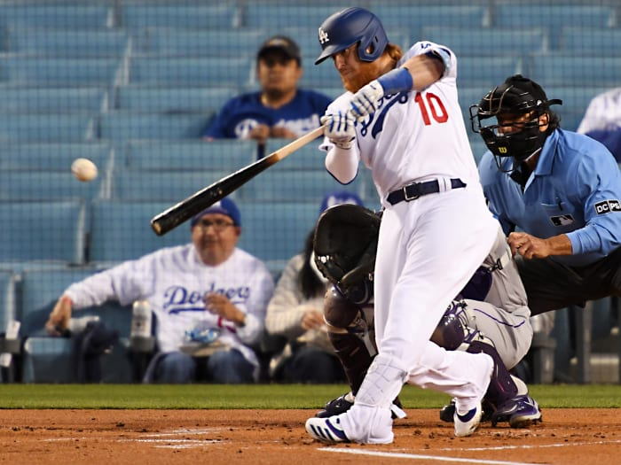 April 14, 2021;  Los Angeles, California, United States;  Los Angeles Dodgers third baseman Justin Turner (10) singles in a run in the first inning of the game against the Colorado Rockies at Dodger Stadium.