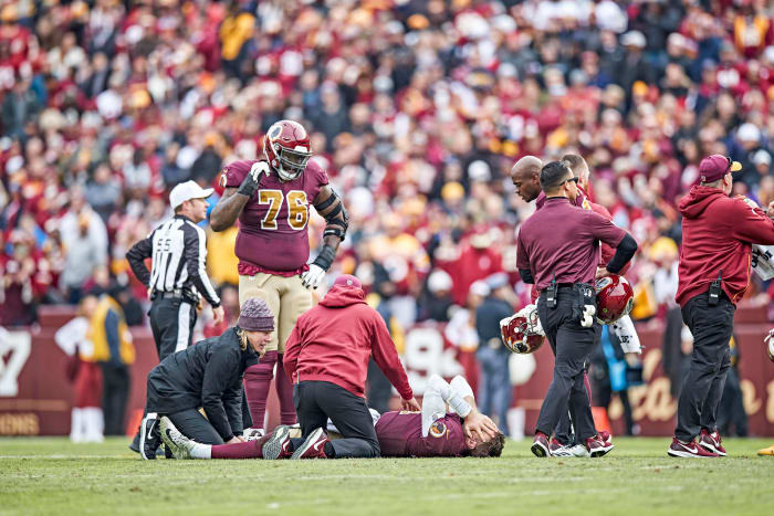 Alex Smith lies on the field with his hands over his face after breaking his right leg during a 2018 game
