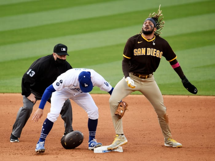 April 25, 2021;  Los Angeles, California, United States;  San Diego Padres shortstop Fernando Tatis Jr. (23) throws his hair after stealing second base against Los Angeles Dodgers second baseman Chris Taylor (3) during the sixth inning at Dodger Stadium.