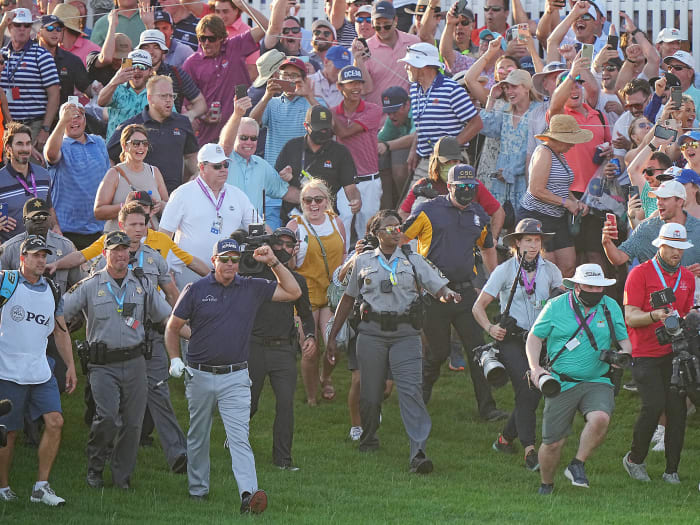 Phil Mickelson walks to the 18th green at the PGA Championship, fist raised, with a crowd of fans behind him.
