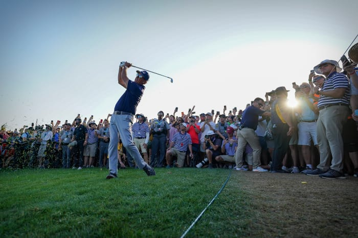 Phil Mickelson hits a chip on the 18th hole as fans huddle behind him during the final round of the PGA Championship golf tournament.