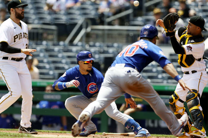 May 27, 2021; Pittsburgh, Pennsylvania, USA;  Pittsburgh Pirates first baseman Will Craig (left) chases Chicago Cubs shortstop Javier Baez (9) in a run-down between home plate and first base allowing catcher Willson Contreras (40) to score a run as Pirates catcher Michael Perez (right) takes a throw during the third inning at PNC Park.