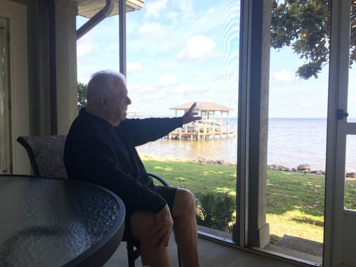 Pete Jenkins, ein langjähriger Trainer der SEC-Verteidigungslinie, deutet von seinem Haus in der Nähe des 30A-Bereichs auf die Bucht.