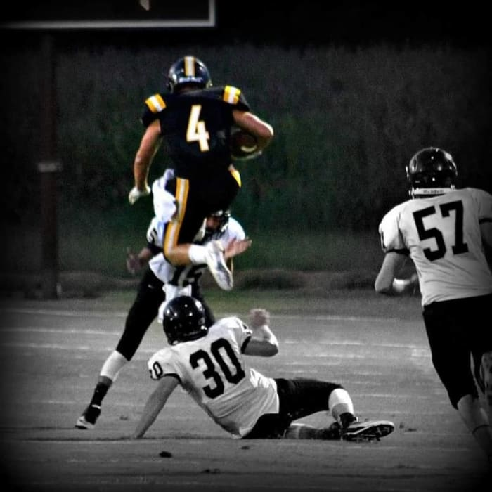Evan Russell (4) leaps over a defender in high school football. Credit: The Jackson Sun/submitted via Russell family