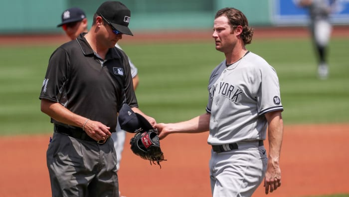 June 27, 2021;  Boston, Massachusetts, United States;  Umpires check the hat and glove of New York Yankees starting pitcher Gerrit Cole (45) during the first inning against the Boston Red Sox at Fenway Park.