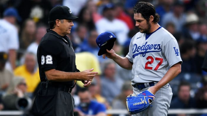 June 23, 2021;  San Diego, California, United States;  Los Angeles Dodgers starting pitcher Trevor Bauer (27) is checked for unauthorized foreign substances by referee James Hoye (92) during the first inning at Petco Park.