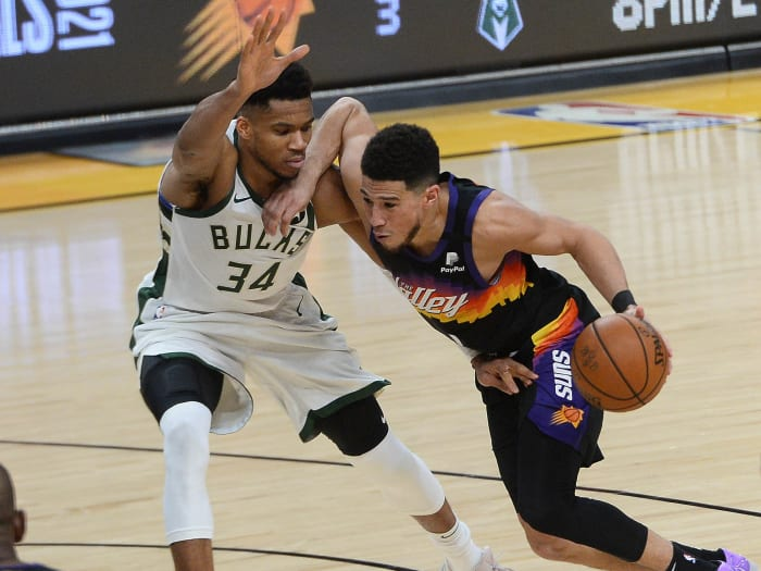 Phoenix Suns guard Devin Booker (1) moves the ball against Milwaukee Bucks forward Giannis Antetokounmpo (34) during the second half of game two of the 2021 NBA Finals at Phoenix Suns Arena .