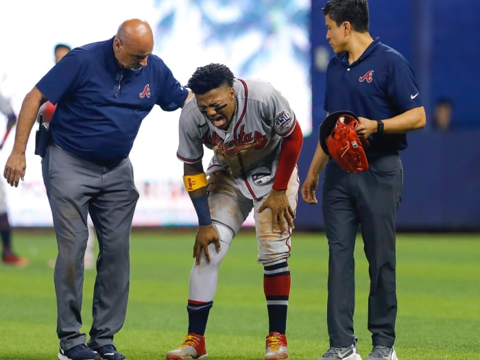 Atlanta Braves right fielder Ronald Acuña Jr. (13) reacts when coaching staff control him after an apparent leg injury during the fifth inning against the Miami Marlins at Loan Depot Park.