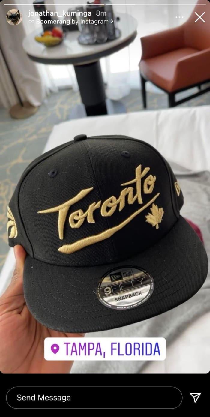 Jonathan Kuminga holding a Toronto Raptors hat