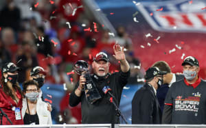 Bucs coach Bruce Arians addresses the crowd from the podium while holding the Lombardi Trophy after Super Bowl LV