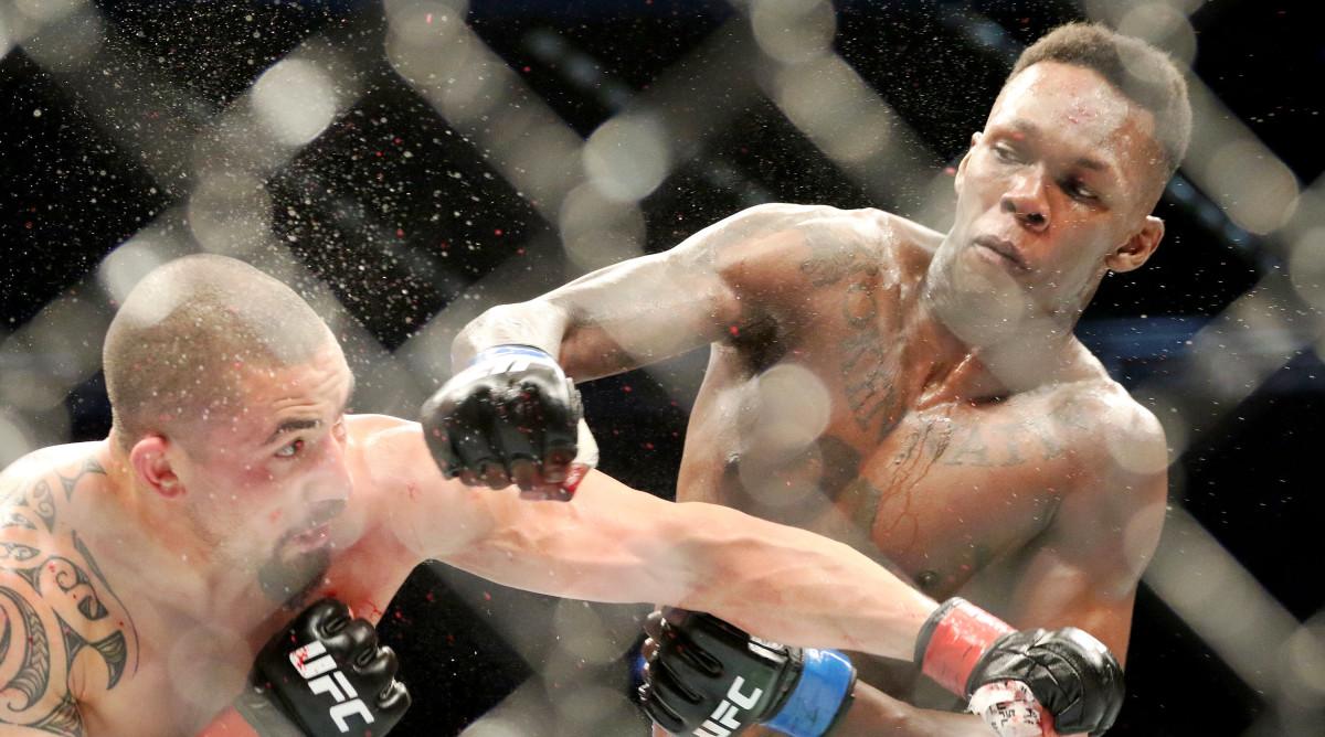 Oct 5, 2019; Melbourne, AUSTRALIA; Israel Adesanya (blue gloves) and Robert Whittaker (red gloves) during UFC 243 at Marvel Stadium. Mandatory Credit: Jasmin Frank-USA TODAY Sports