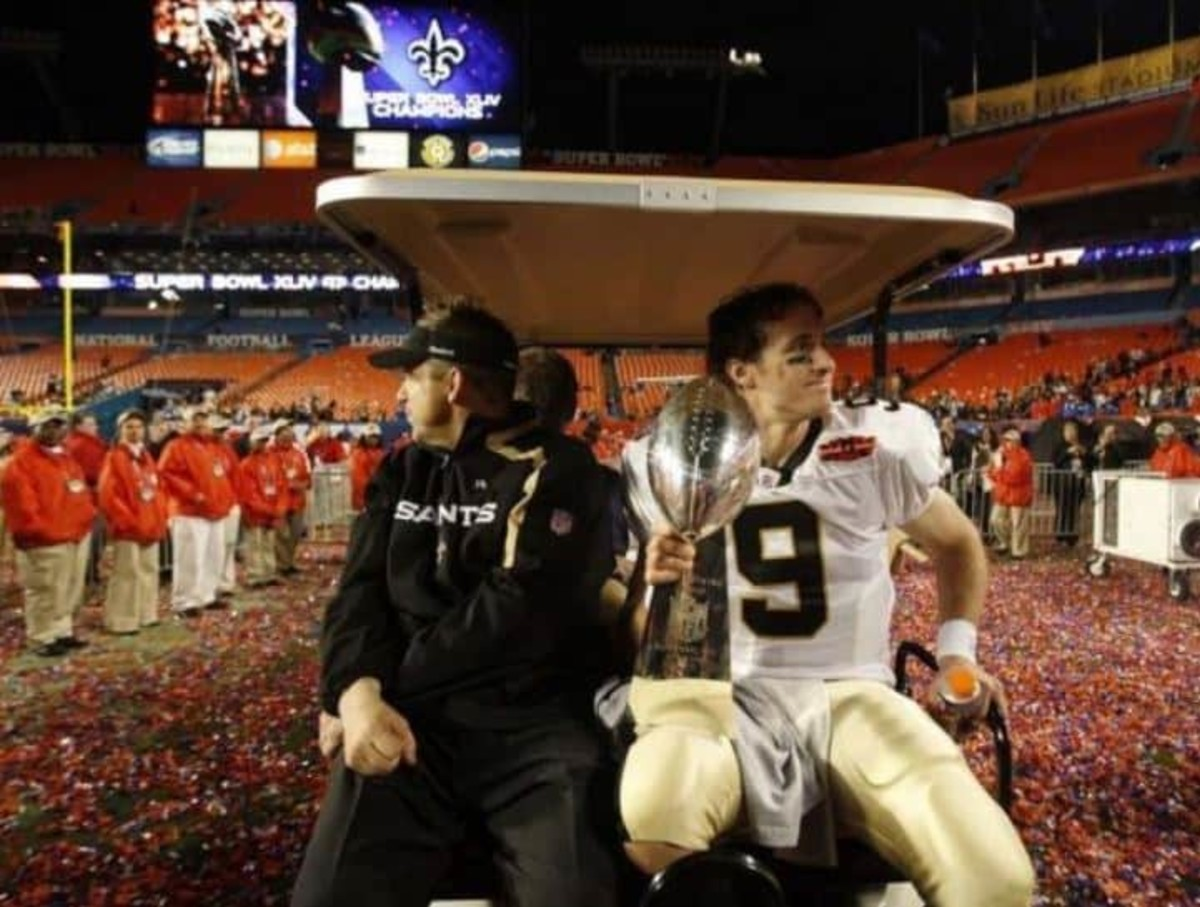 Feb 7, 2010 ; Miami Gardens, FL, USA; New Orleans Saints head coach Sean Payton shares a ride with quarterback Drew Brees (9) (holding the Lombardi Trophy) as they leave the field after defeating the Indianapolis Colts 31-17 in Super Bowl XLIV at Sun Life Stadium in Miami Gardens, Florida. Mandatory Credit: Matthew Emmons-US PRESSWIRE