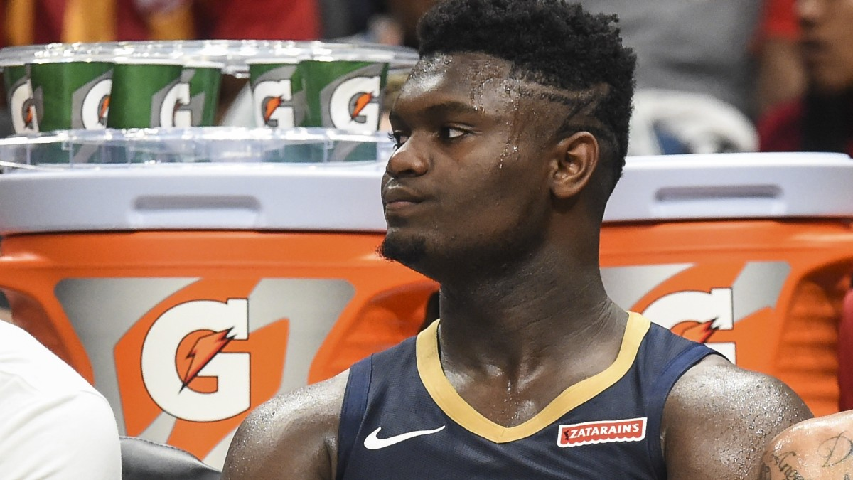 Zion Williamson sits on the Pelicans bench during preseason.